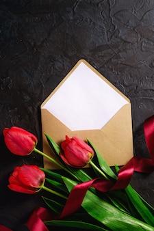 Bouquet de fleurs de tulipe rouge avec carte enveloppe et ruban sur mur noir texturé, vue de dessus copie espace