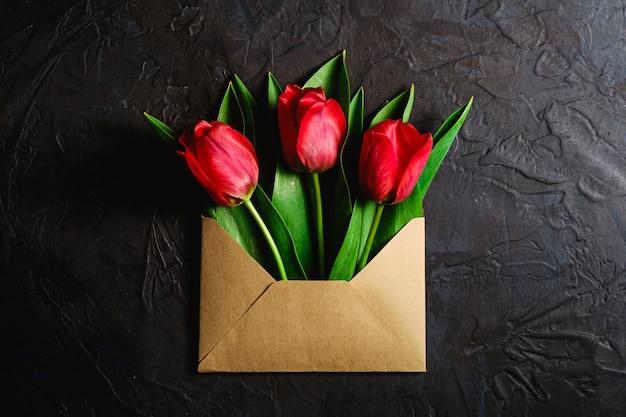 Bouquet de fleurs de tulipe rouge dans une enveloppe en papier sur fond noir foncé texturé, vue de dessus copie espace