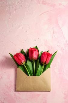Bouquet de fleurs de tulipe rouge dans une enveloppe en papier sur fond rose texturé, vue de dessus copie espace