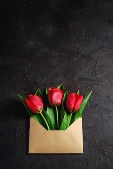 Bouquet de fleurs de tulipe rouge dans une enveloppe en papier sur un mur noir foncé texturé, vue de dessus copie espace