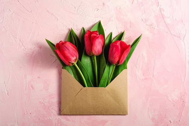 Bouquet de fleurs de tulipe rouge dans une enveloppe en papier sur une surface rose texturée, vue de dessus copie espace