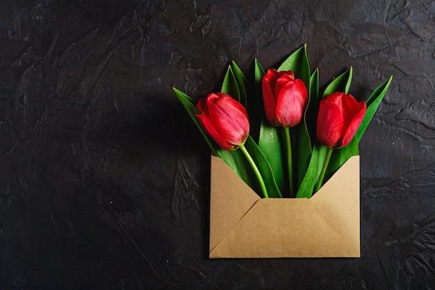 Bouquet de fleurs de tulipe rouge dans une enveloppe en papier