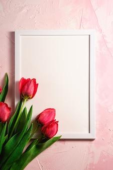 Bouquet de fleurs de tulipe rouge avec modèle de cadre photo sur une surface rose texturée, vue de dessus copie espace