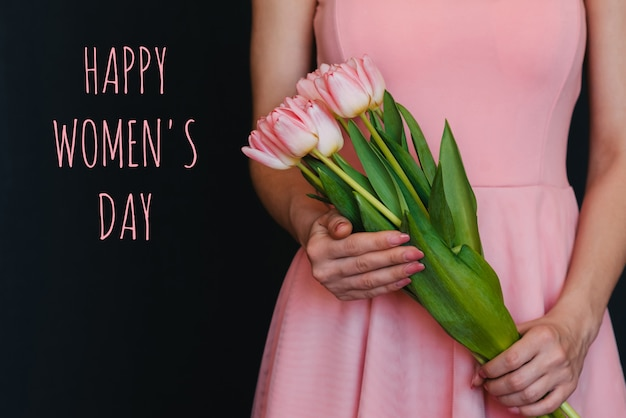 Bouquet de fleurs de tulipes roses dans les mains d'une fille