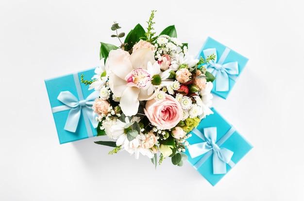 Bouquet de fleurs vue de dessus sur fond blanc avec des coffrets cadeaux à plat