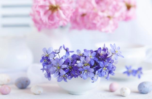 Bouquet frais de délicates fleurs printanières de l'hépatique hepatica nobilis dans un vase blanc