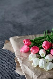 Bouquet frais de tulipes blanches et roses sur du papier recyclé sur fond gris