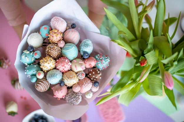 Un bouquet de fraises enrobées de chocolat dans les mains de la femme