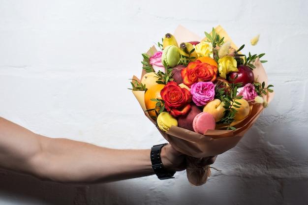 Un bouquet de fruits et de fleurs est offert par un homme sur fond blanc