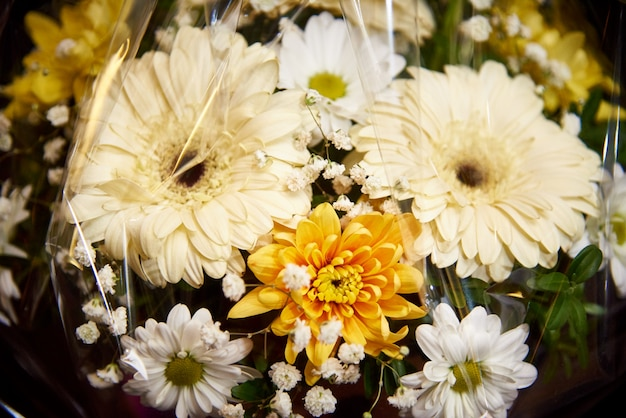 Un bouquet de gerberas blancs et de marguerites dans l'emballage.