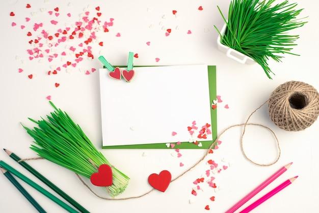 Un bouquet de germes de blé vert, enveloppes, crayons et coeurs sur fond clair.
