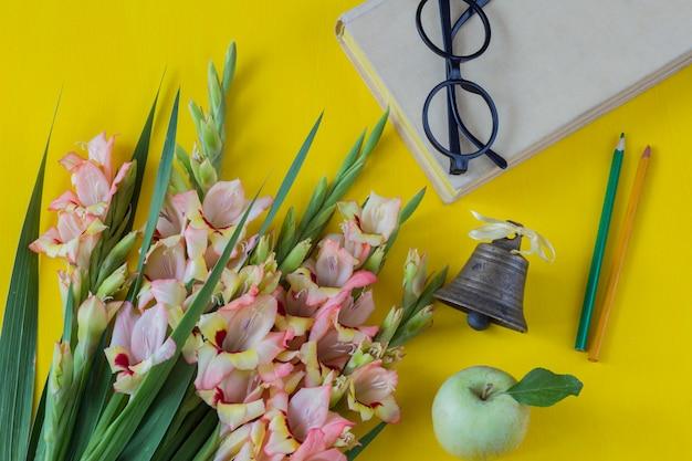 Un bouquet de glaïeuls, un livre, des lunettes, une pomme verte, deux crayons et une vieille clochette