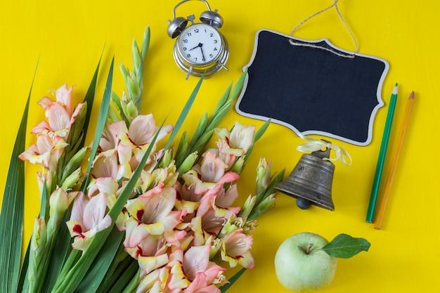 Un bouquet de glaïeuls, une pomme verte, deux crayons, un disque et une vieille cloche