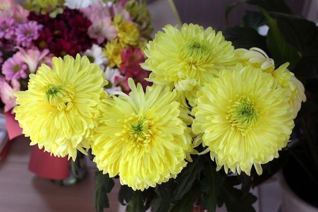 Un bouquet de gros chrysanthèmes jaunes se dresse sur la table près d'autres fleurs.