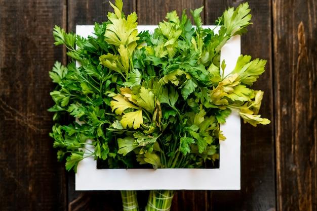 Bouquet d'herbes de persil vert cru frais avec cadre carré blanc sur le dessus de l'espace de copie créatif f