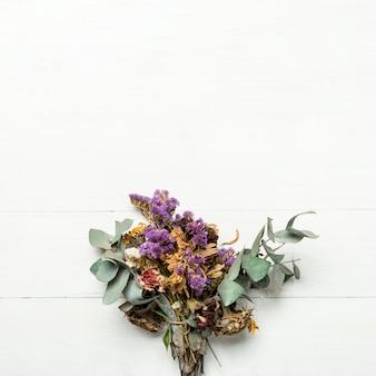 Bouquet d'herbes séchées et de fleurs sur une surface blanche