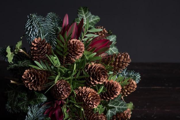 Bouquet d'hiver de brindilles de sapin nobil, cônes, pistache, leucodendron et lierre, concept de cadeau d'hiver
