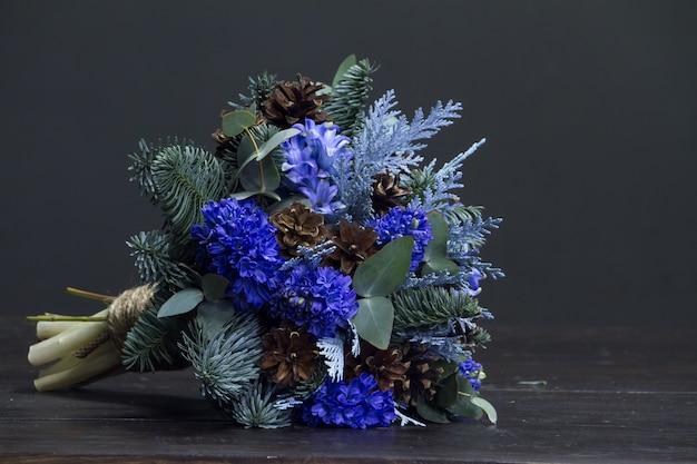 Bouquet d'hiver de brindilles de sapin nobil, jacinthes et cônes bleus, concept de cadeau d'hiver
