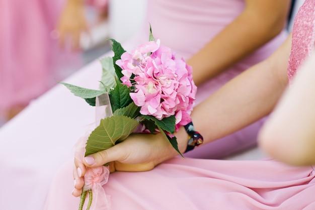 Bouquet d'hortensia rose dans les mains d'une jeune fille en gros plan d'une robe rose. bouquet de demoiselle d'honneur au mariage