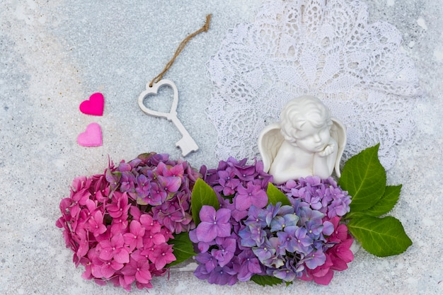 Un bouquet d'hortensias, un ange en céramique, deux coeurs et une clé en bois
