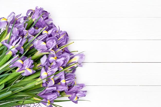 Bouquet d'iris sur un fond en bois blanc.