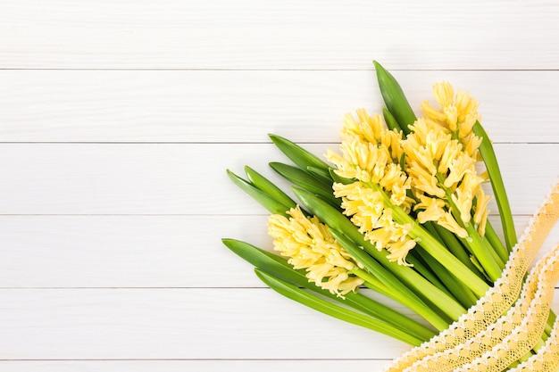 Bouquet de jacinthes jaunes décorées avec de la dentelle sur un fond en bois blanc. vue de dessus, espace de copie