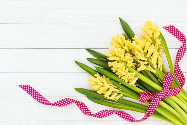 Bouquet de jacinthes jaunes décorées avec un ruban rouge. vue de dessus, surface
