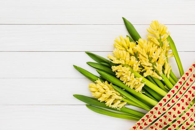 Bouquet de jacinthes jaunes sur fond en bois blanc.