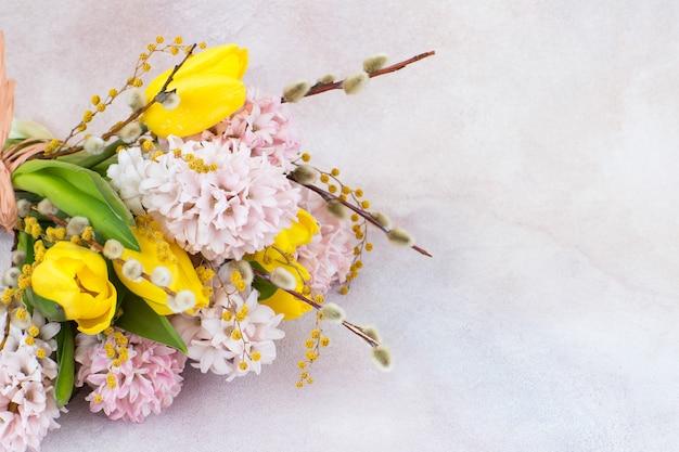 Bouquet de jacinthes roses et tulipes jaunes, mimosa et saule et espace libre pour le texte