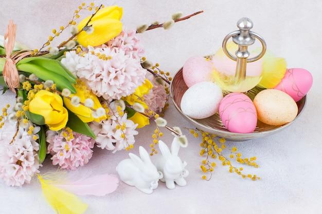Un bouquet de jacinthes et de tulipes, deux figures de lapins et des oeufs de pâques dans un vase
