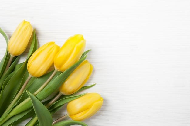 Bouquet jaune de tulipes sur fond en bois blanc. affiche de printemps avec espace de texte libre.