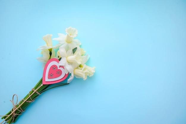 Un bouquet de jonquilles avec un coeur sur un bm bleu,