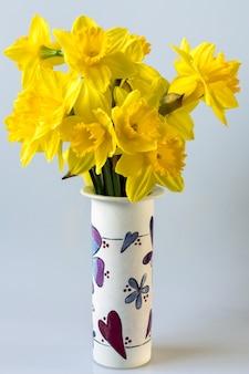Un bouquet de jonquilles dorées dans un vase en céramique décoré