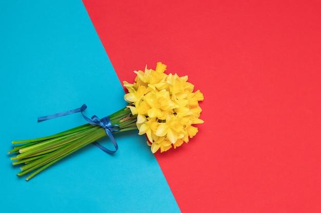Bouquet de jonquilles jaunes fraîches dans des mains féminines sur fond avec un espace pour le texte
