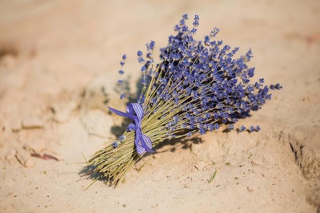Bouquet de lavande attaché avec un ruban allongé sur le sable