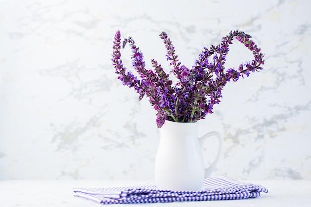 Un bouquet de lavande parfumée fraîche dans un pot blanc sur la table. couleurs blanches et violettes. décoration d'intérieur. espace de copie