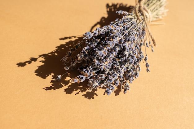 Bouquet de lavande sèche pilée avec une corde naturelle sur fond beige. aromathérapie et médecine alternative.