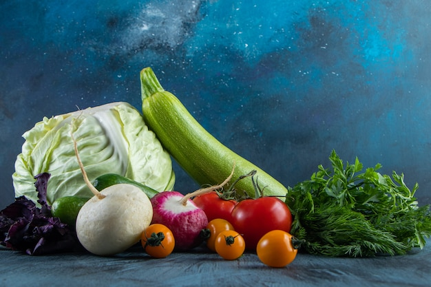 Bouquet de légumes frais mûrs placés sur fond bleu.