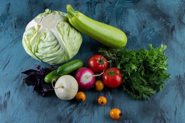 Bouquet de légumes frais mûrs placés sur une surface bleue.