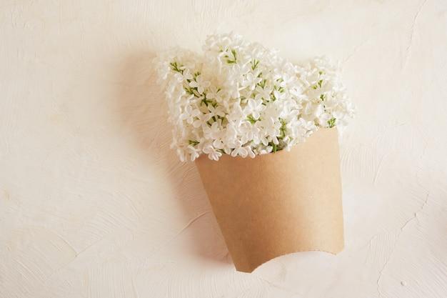 Un bouquet de lilas blancs dans un emballage de frites sur fond beige copie espace vue de dessus