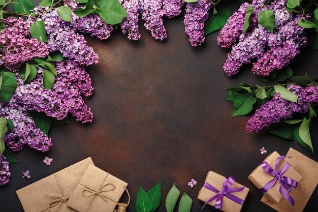 Un bouquet de lilas avec boîte-cadeau, enveloppe de bricolage sur fond rouillé. fête des mères