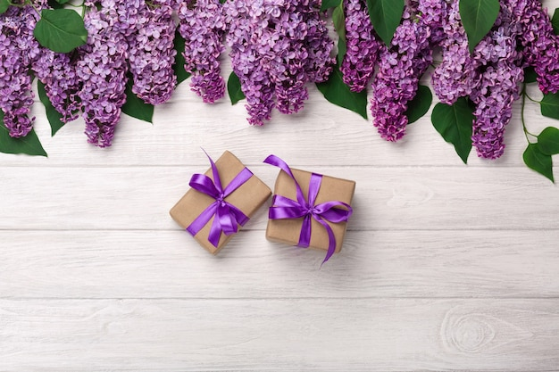Un bouquet de lilas avec une boîte cadeau sur des tableaux blancs. fête des mères