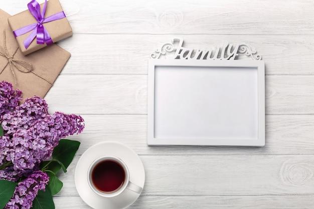Un bouquet de lilas avec un cadre blanc pour inscription, tasse de thé, boîte-cadeau, enveloppe de bricolage sur des tableaux blancs