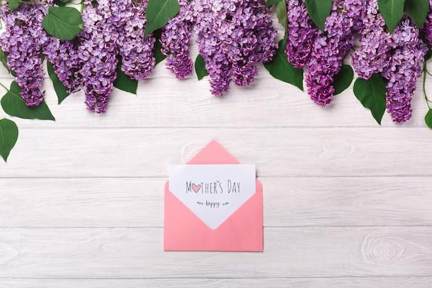 Un bouquet de lilas et une enveloppe de couleur avec une note d'amour sur des tableaux blancs. fête des mères