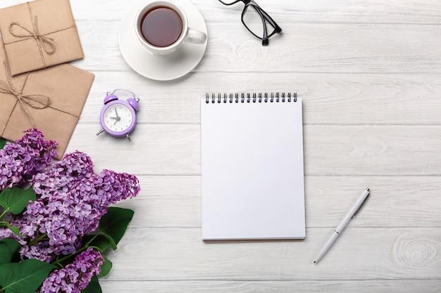 Un bouquet de lilas avec une tasse de thé, un cahier, un réveil, des enveloppes artisanales sur des tableaux blancs. fête des mères