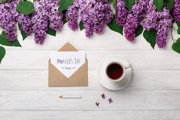 Un bouquet de lilas avec une tasse de thé, une enveloppe artisanale et une note d'amour sur des tableaux blancs. fête des mères