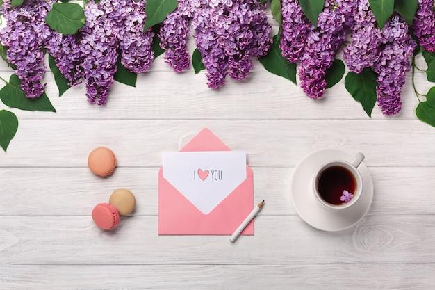 Un bouquet de lilas, une tasse de thé, une note d'amour et des macarons sur une table en bois blanche