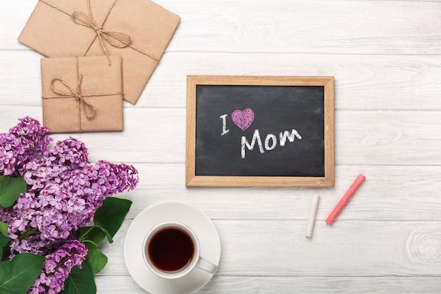 Un bouquet de lilas avec une tasse de thé, un tableau noir, une enveloppe d'artisanat, une note d'amour sur des tableaux blancs. fête des mères