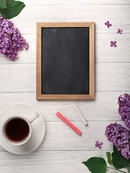 Un bouquet de lilas avec une tasse de thé, un tableau noir sur des tableaux blancs. fête des mères