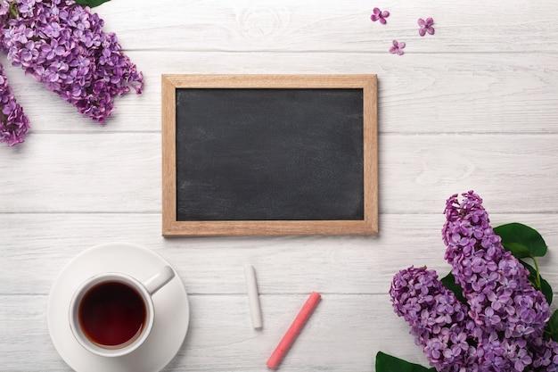 Un bouquet de lilas avec une tasse de thé, un tableau noir sur des tableaux blancs